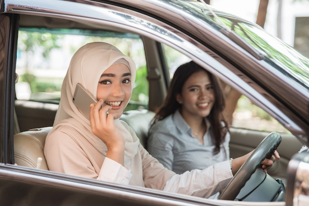Молодая женщина за рулем своего автомобиля с помощью мобильного телефона