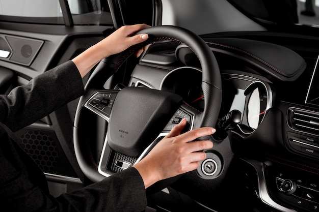 Young woman driving inside a luxury car, holding the steering wheel