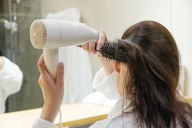 Молодая женщина сушит волосы феном и укладывает волосы круглой щеткой для волос в ванной комнате