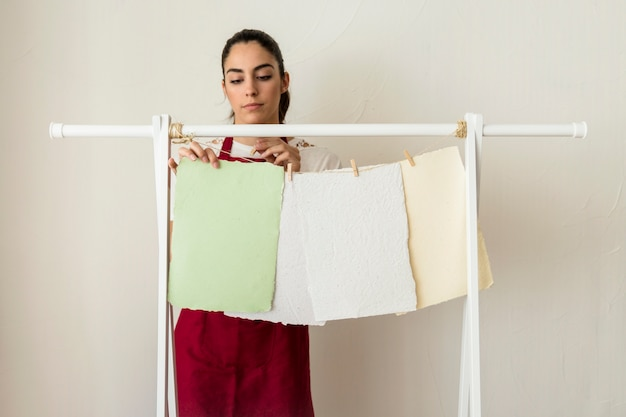 Young woman drying handmade papers with clothespin