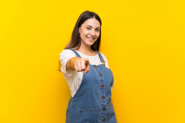 Young woman in dungarees points finger at you with a confident expression