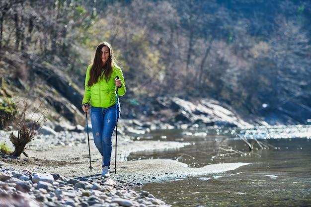 Молодая женщина во время похода по скандинавской ходьбе на берегу реки