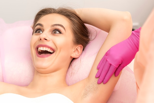 뷰티 살롱에서 웃고 절차를 왁싱하기 전에 겨드랑이 검사를하는 동안 젊은 여자