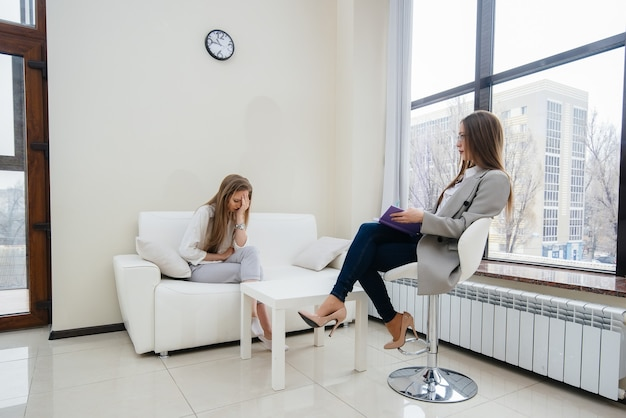 A young woman during depression communicates with a psychologist in the office