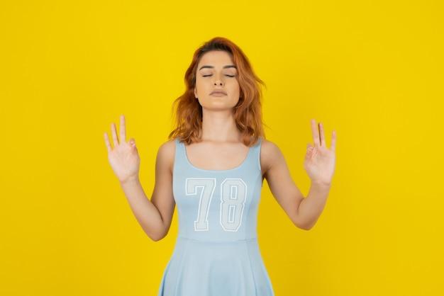Молодая женщина во время медитации на желтом.