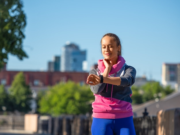 Young woman during the morning jog measures the pulse by checking the watches
