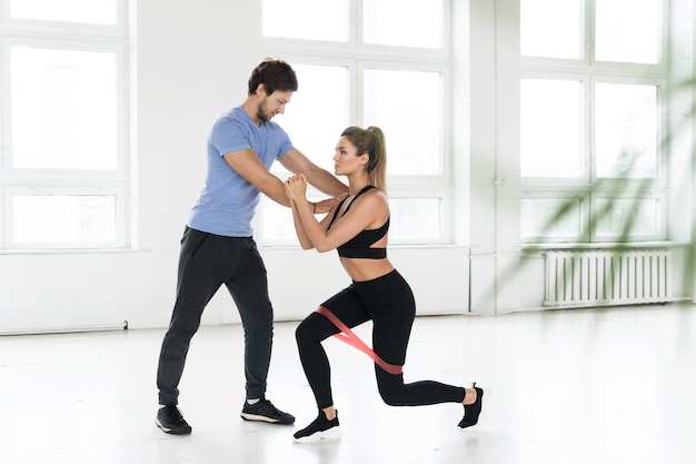 체육관에서 고무 저항 밴드를 사용하여 개인 피트니스 강사와 함께 운동하는 동안 젊은 여자.
