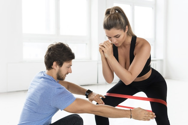 Young woman during workout with a personal fitness instructor using rubber resistance bands in the gym.