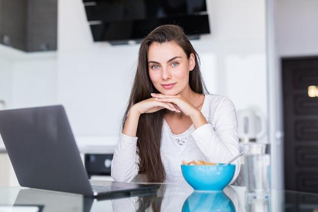 Молодая женщина ест салат работает на ноутбуке на кухне
