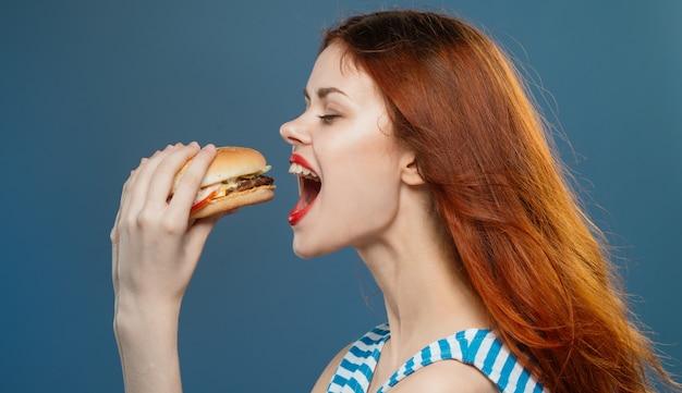 수분이 많은 햄버거, 스튜디오에서 맛있는 패스트 푸드 햄버거를 먹는 젊은 여자