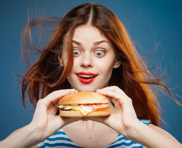 ジューシーなハンバーガー、スタジオでおいしいファーストフードのハンバーガーを食べる若い女性