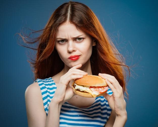 Молодая женщина ест сочный гамбургер, вкусный фаст-фуд гамбургер