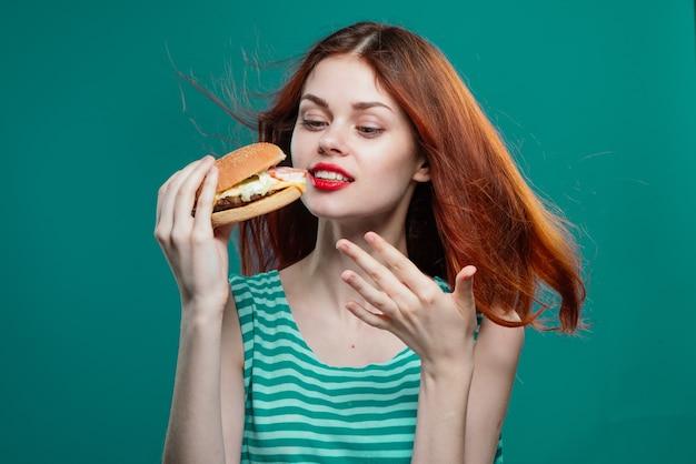 Молодая женщина ест сочный бургер