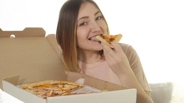 食欲をそそるピザを食べる若い女性。カロリー食品。