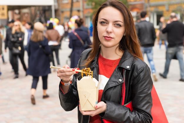忙しいお祭りでアジアのテイクアウトを食べる若い女性