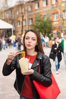 바쁜 축제에서 아시아 테이크 아웃을 먹는 젊은 여자