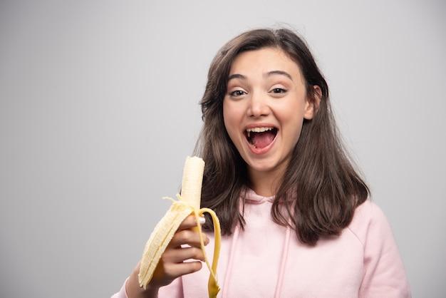 灰色の壁にバナナを食べる若い女性。