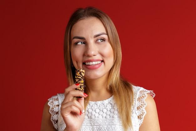 シリアルキャンディーバーを食べる若い女性