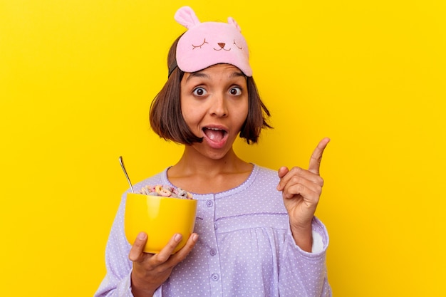 Young woman eating cereals wearing a pijama isolated on yellow wall having an idea