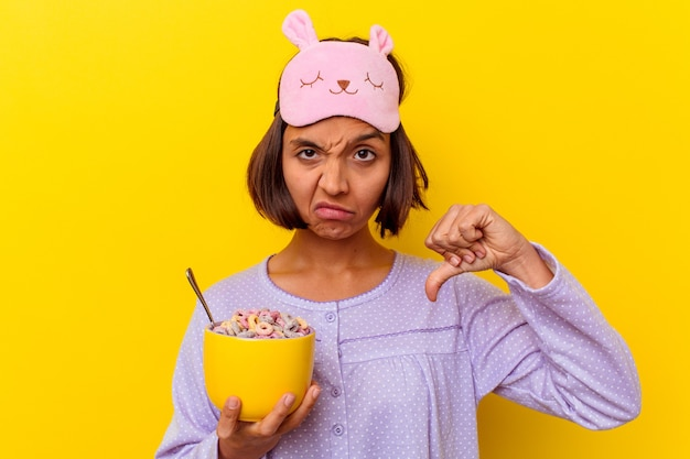 Young woman eating cereals wearing a pijama isolated on yellow wall showing a dislike gesture, thumbs down