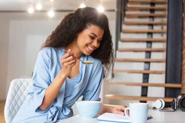Молодая женщина ест злаки