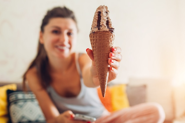 Young woman eating chocolate ice-cream in cone sitting on couch at home.