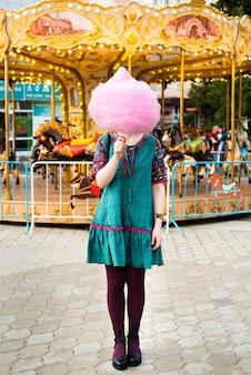 遊園地で綿菓子を食べる若い女性