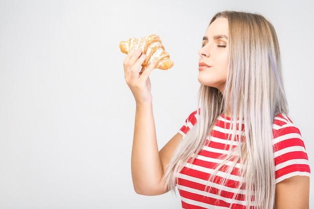 Молодая женщина ест круассан, кофе-брейк