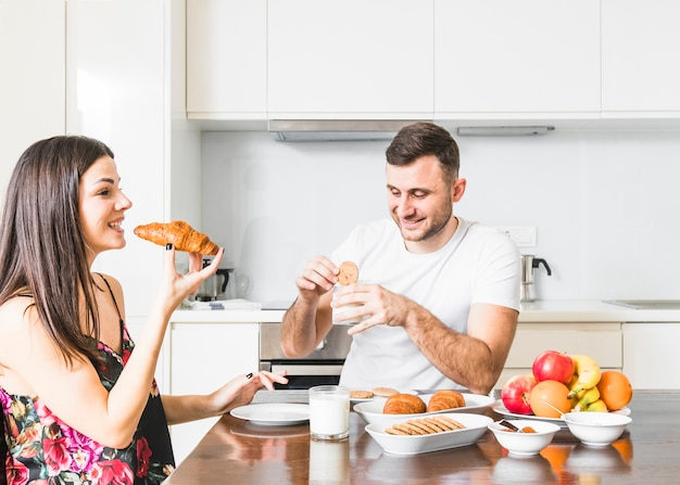 Young woman eating croissant and her husband eating cookies in the kitchen