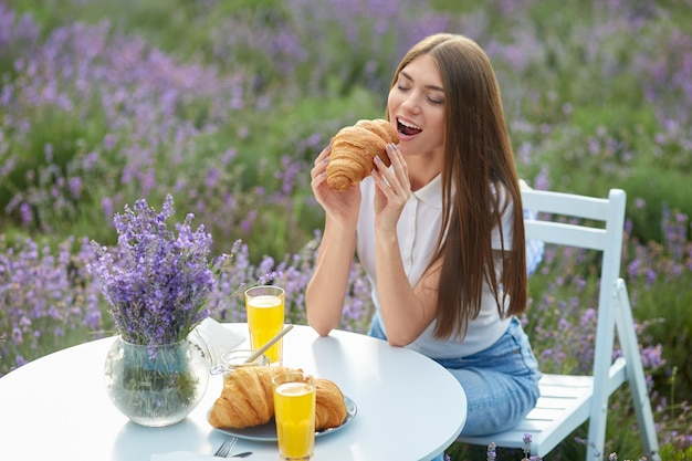 Young woman eating croissant in lavender field