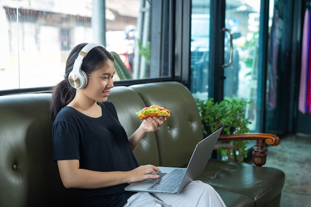 Young woman eating croissant sandwiches in office room