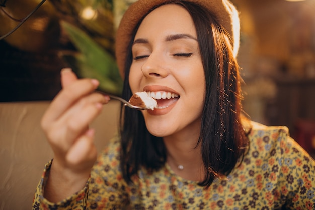 Young woman eating delicious tiramisu in a cafe