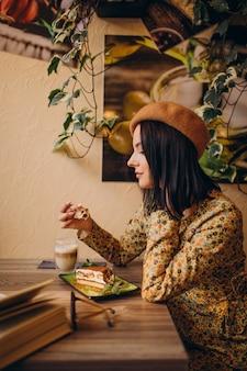 Giovane donna che mangia delizioso tiramisù in un caffè