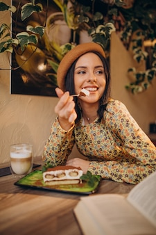 カフェで美味しいティラミスを食べる若い女性