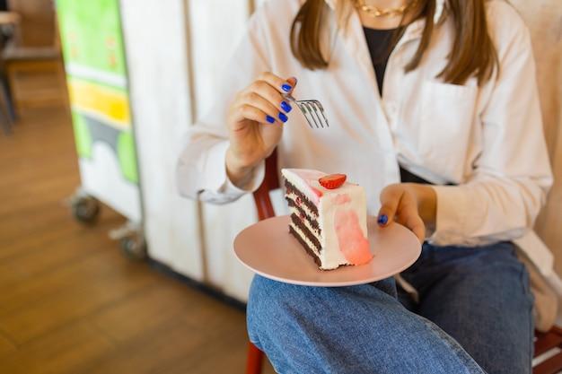 レストランでデザートを食べる若い女性のクローズアップピースoでフォークを保持している女性の手の上面図...