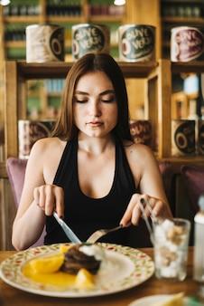 Молодая женщина, едят десерт с вилкой масло нож