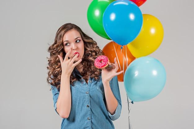 Giovane donna che mangia ciambella e che tiene palloncini colorati sulla parete grigia dello studio