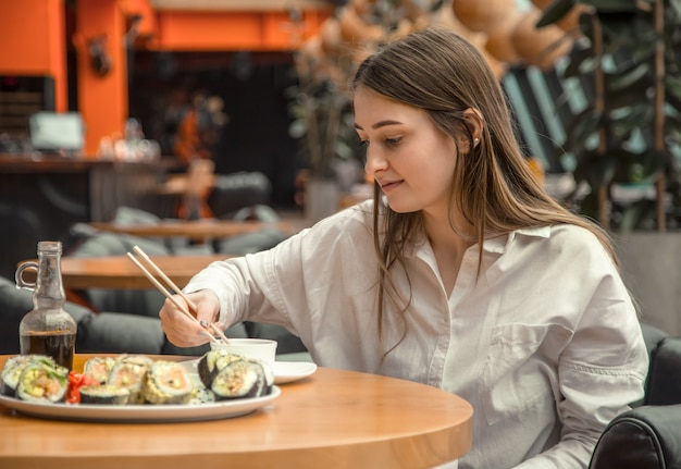Giovane donna che mangia e che gode dei sushi freschi