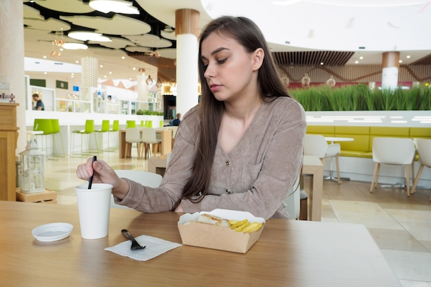 Молодая женщина ест фаст-фуд в ресторане