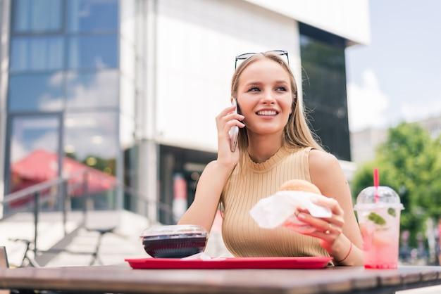 야외 패스트 푸드를 먹고 카페에서 전화 가제트에 말하는 젊은 여자