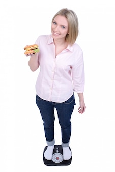 Young woman eating fast food and standing on scales.
