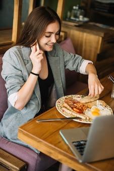 Молодая женщина, едят пищу в ресторане, разговариваете по мобильному телефону