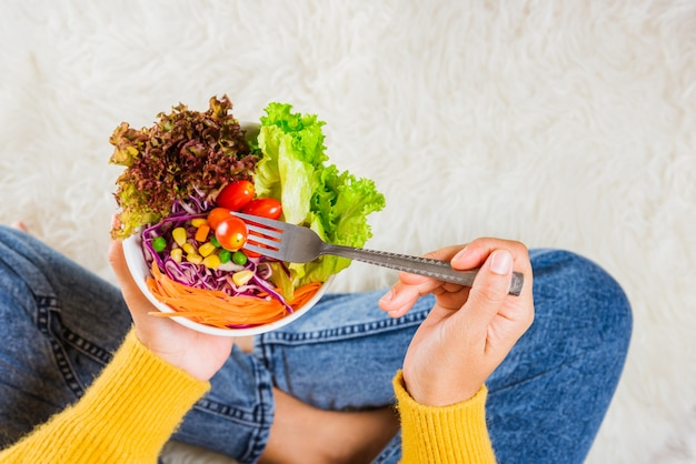 Young woman eating fresh salad meal vegetarian spinach in a bowl