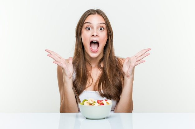 Young woman eating fruit bowl celebrating a victory or success