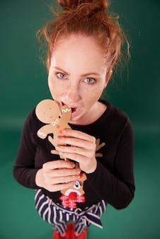 Giovane donna che mangia l'uomo di pan di zenzero