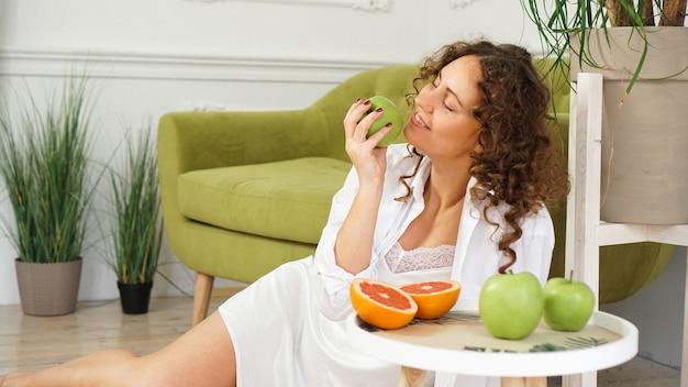 Молодая женщина ест зеленое яблоко дома. здоровое питание, концепция диетического питания. макро портрет красивой молодой женщины, есть органическое зеленое яблоко.