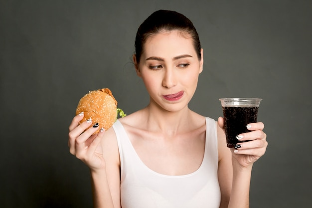 Young woman eating hamburger and cola on gray background