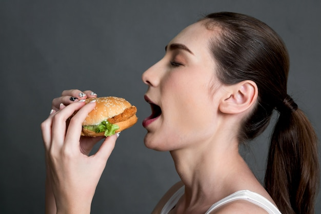 Young woman eating hamburger on gray background