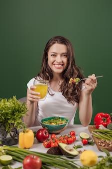緑の背景で健康的な食べ物を食べる若い女性