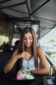 Giovane donna che mangia pasto sano seduto nel bellissimo interno